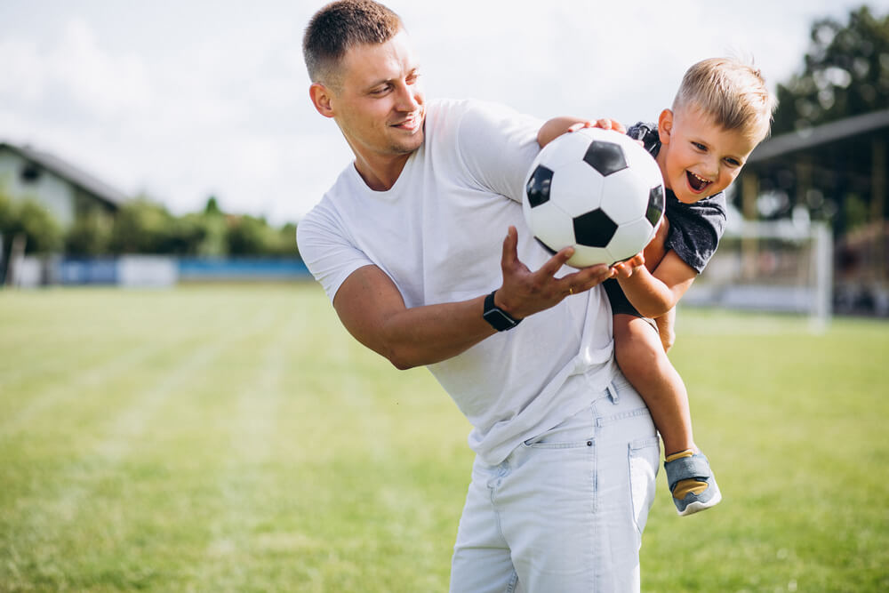 Father playing football with his young son