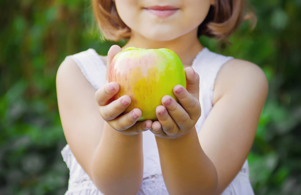 child holding healthy green apple