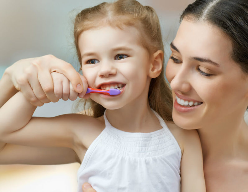 Mother teaching her daughter to brush her teeth