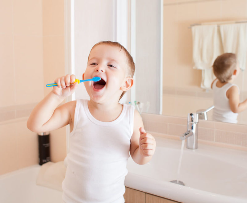 toddler learning how to brush his teeth