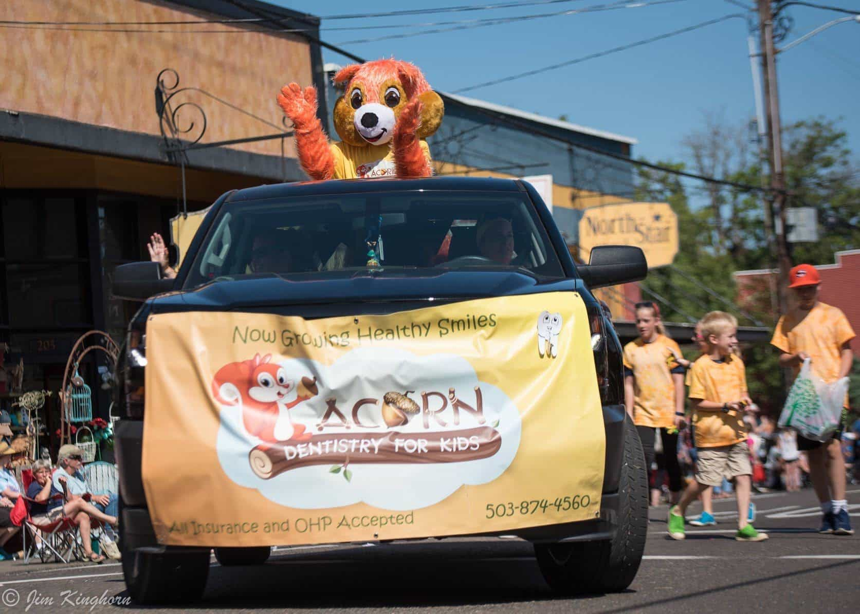 mascot in the back of a truck, promotional banner in the front