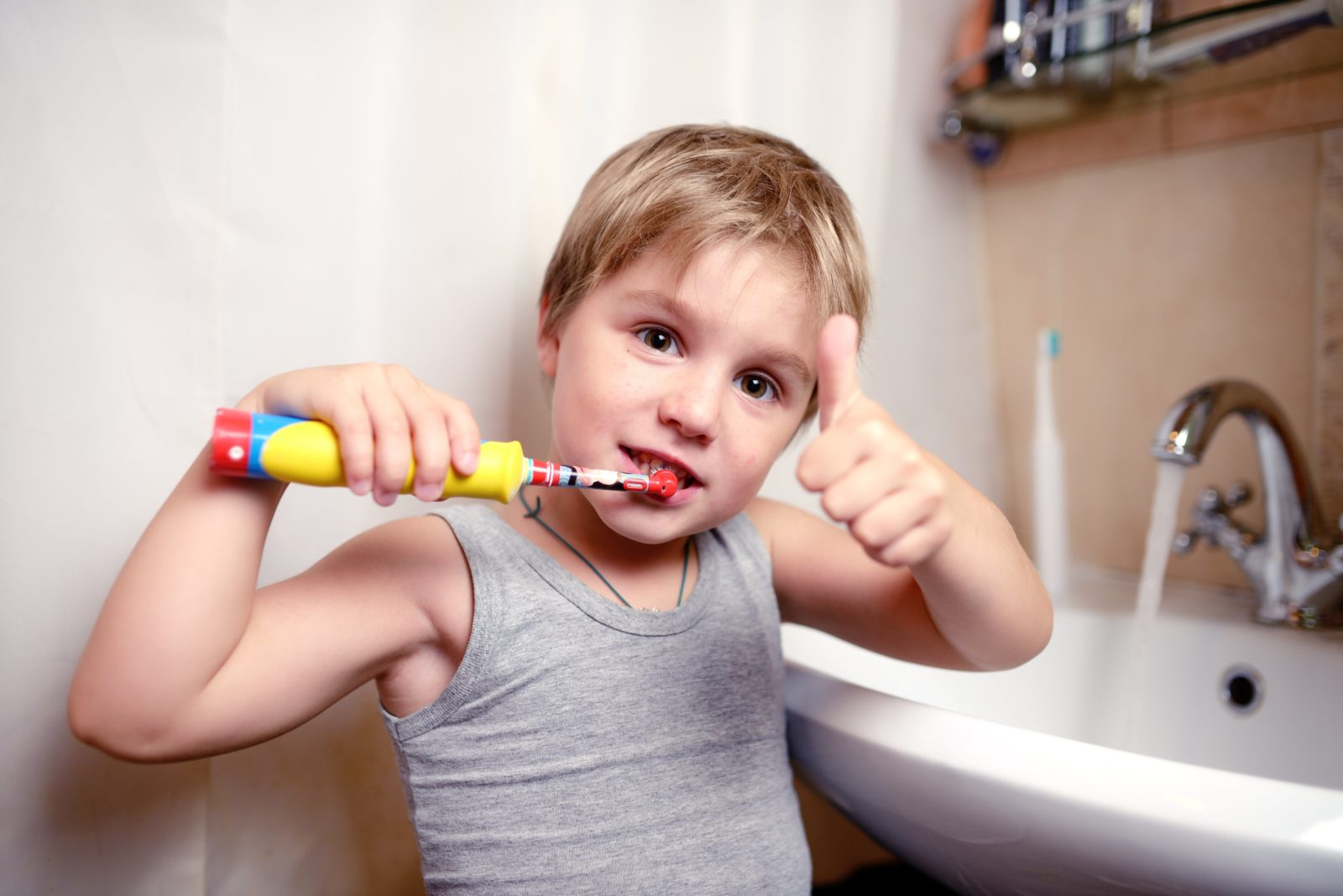 young boy brushing his teeth with a thumbs up
