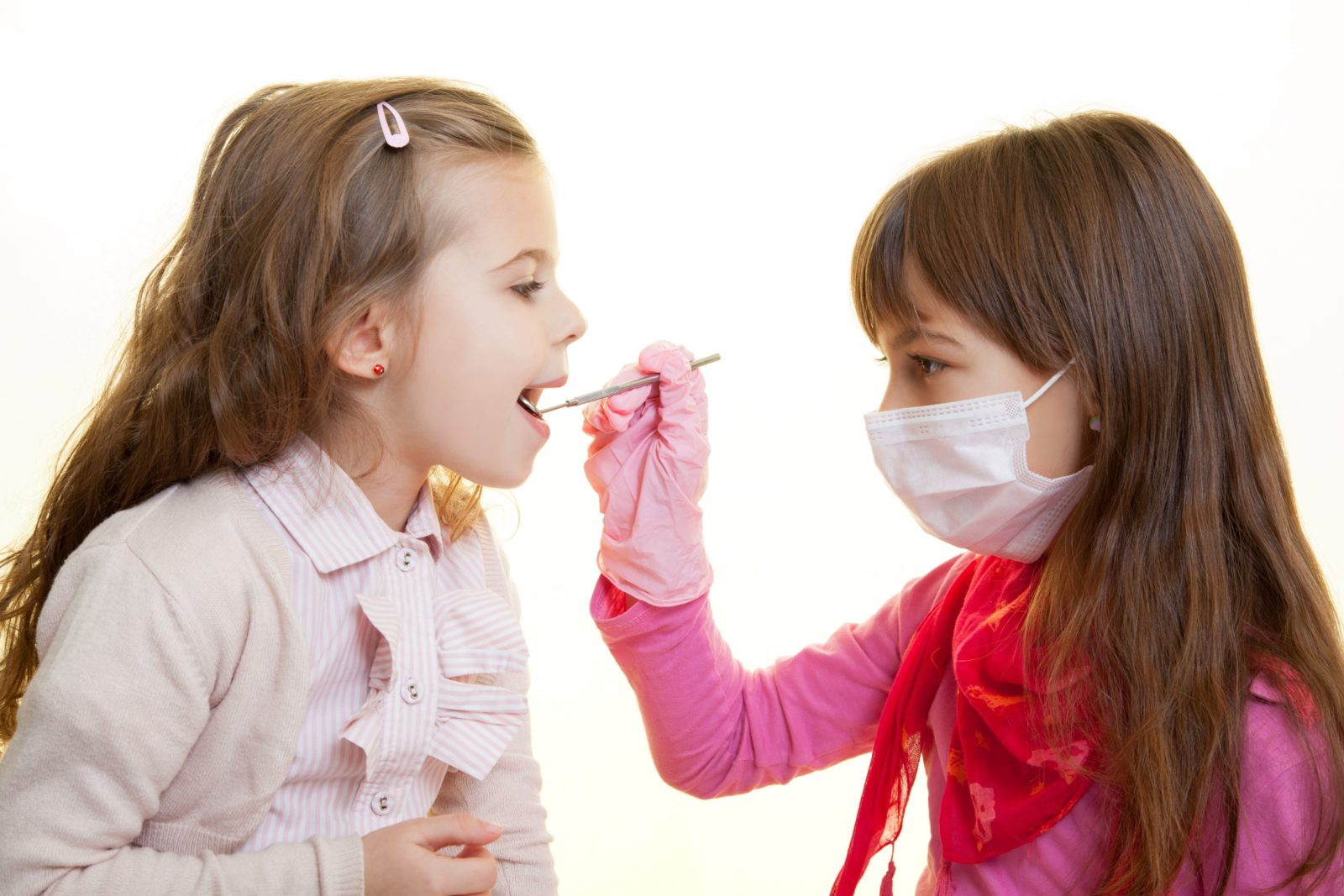 two young girls playing dentist