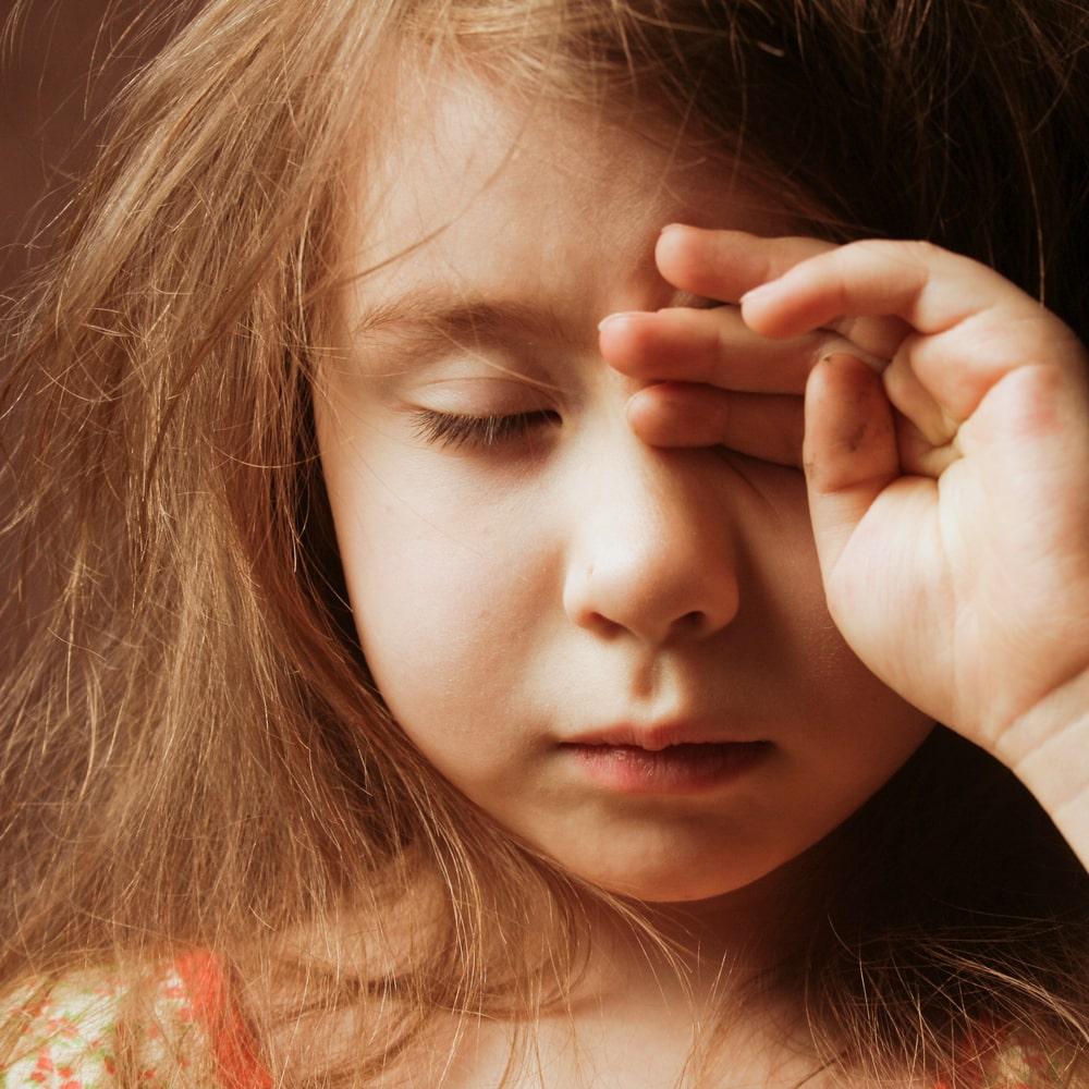 sleepy girl rubbing her eyes
