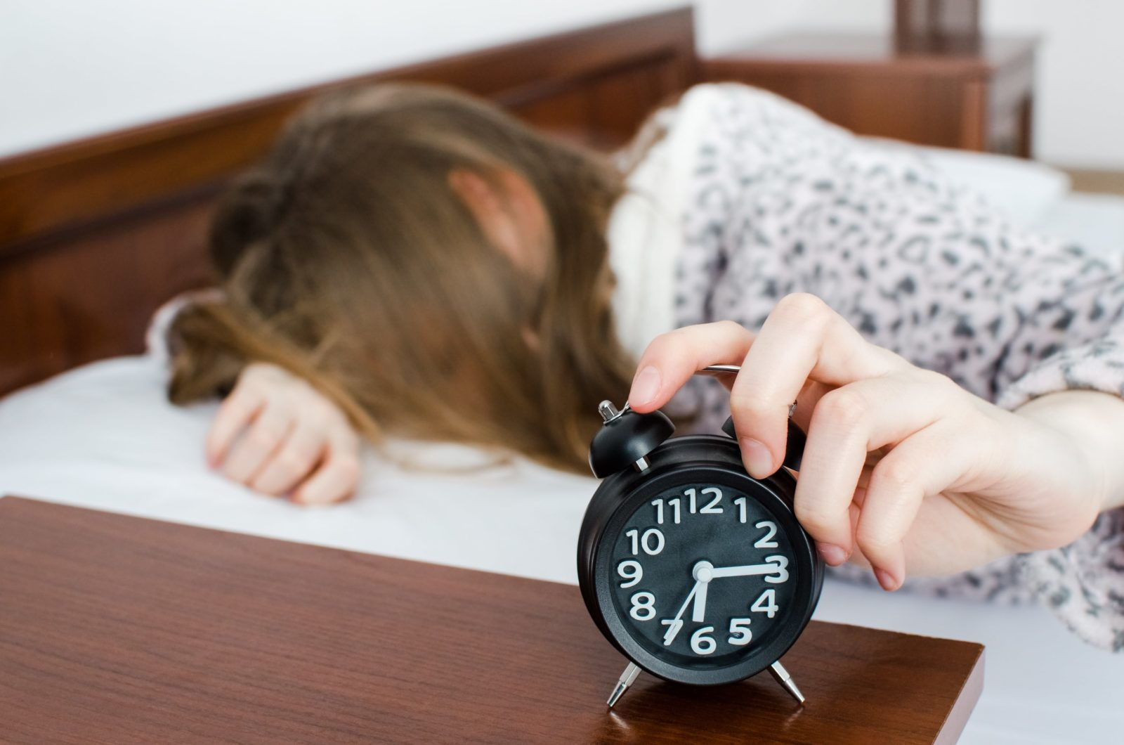 teen girl facedown pressing snooze on her alarm clock