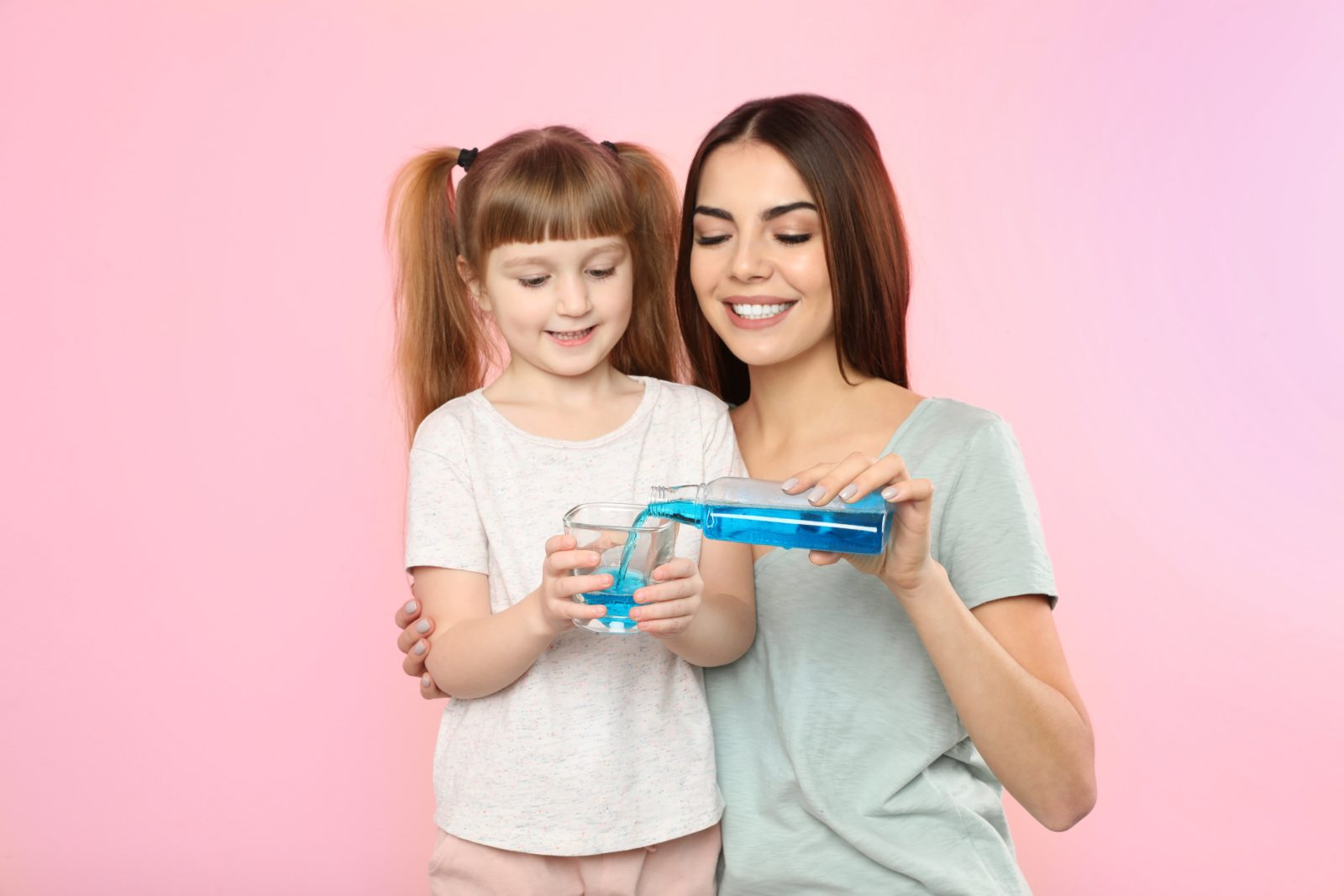 mother helping her daughter with mouthwash