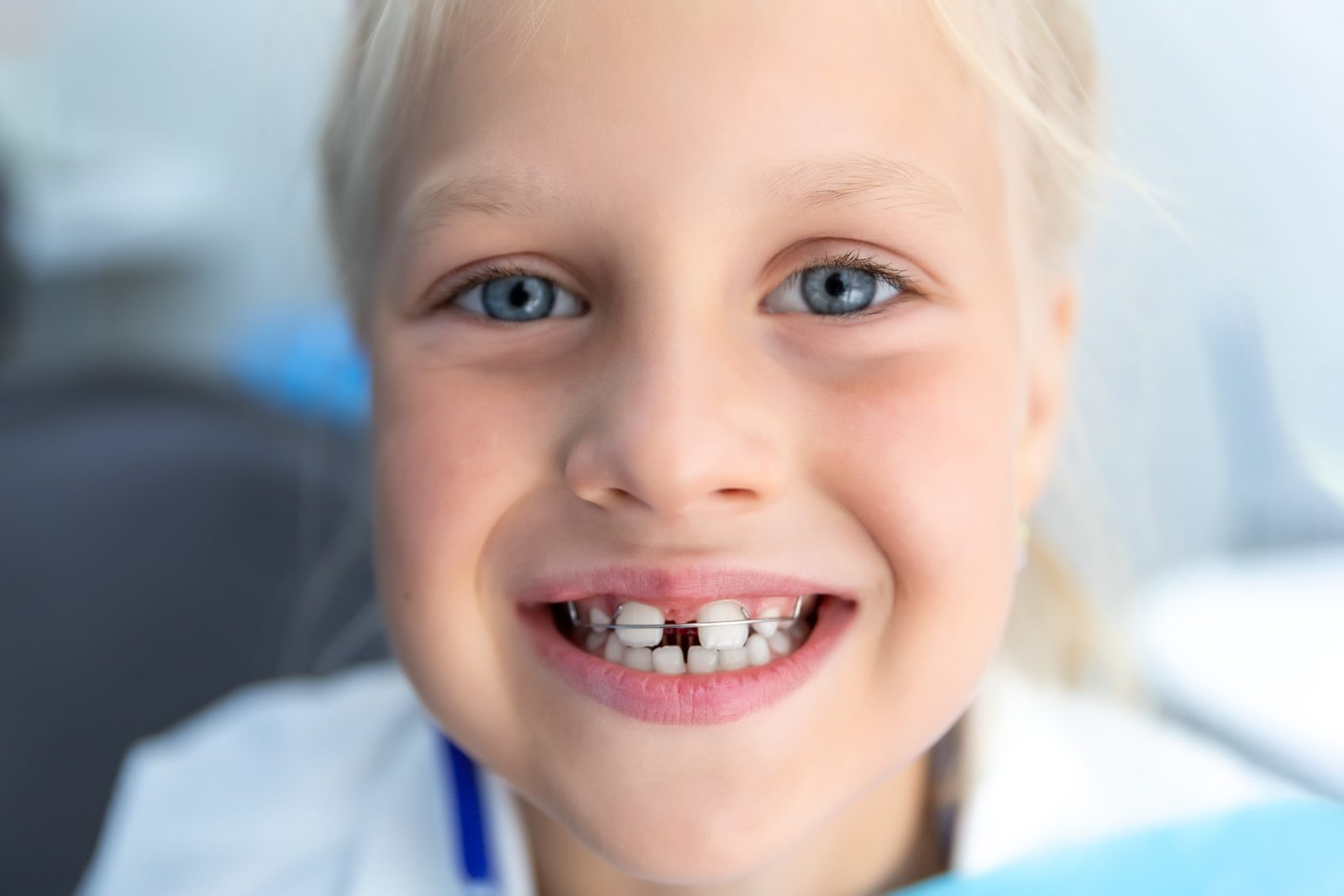 young girl with large gap between her teeth wearing an orthodontic appliance