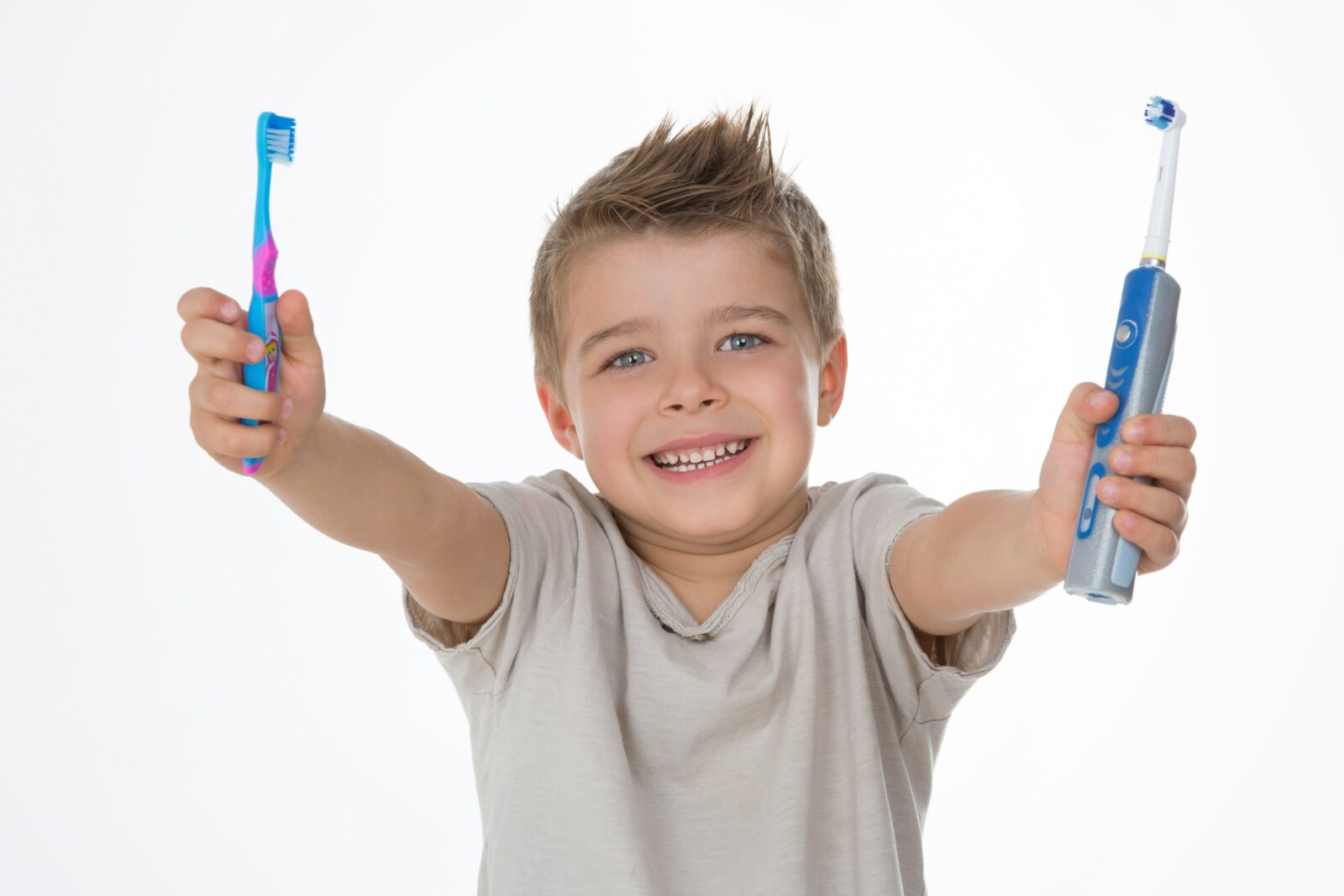 boy holding toothbrushes