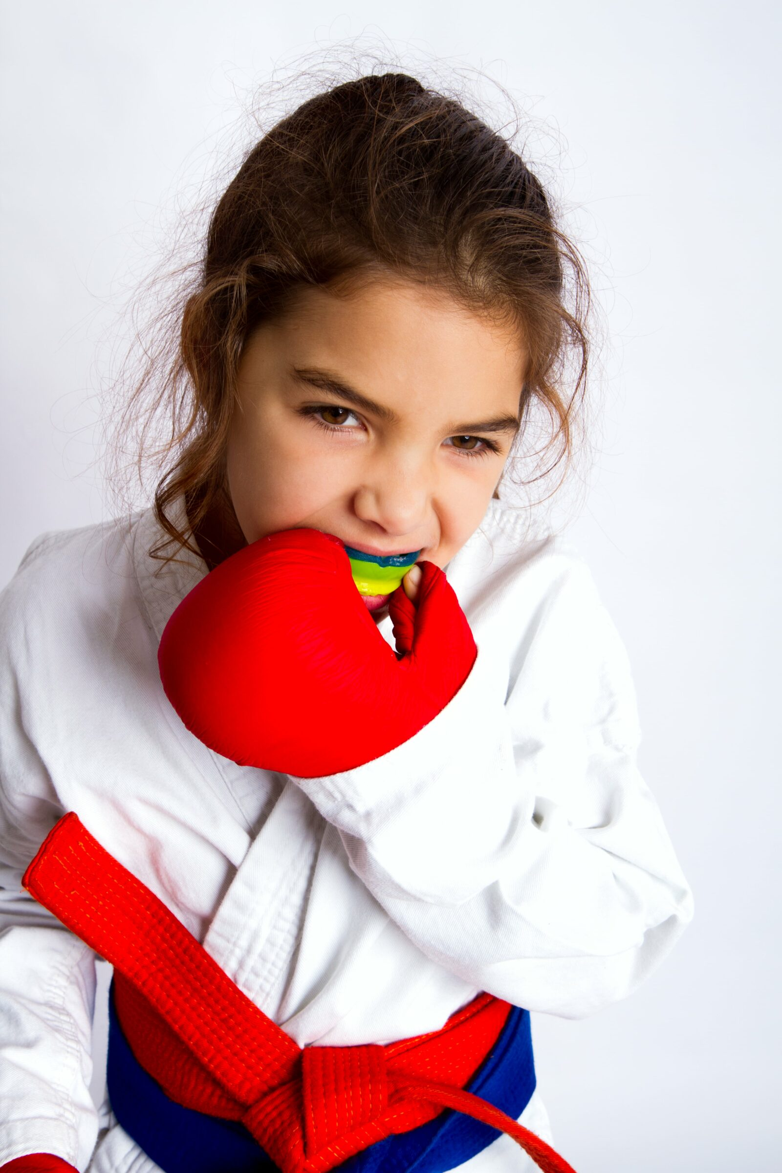 young girl in karate outfit putting in a mouthguard