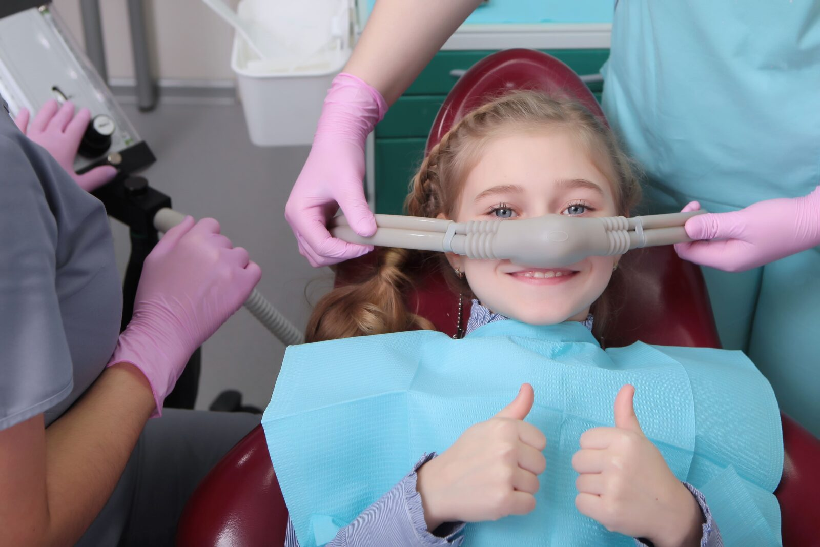 young girl with a nitrous oxide face mask giving a thumbs up
