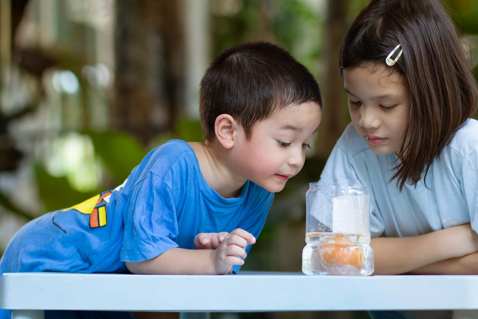 two kids looking at an egg in a jar