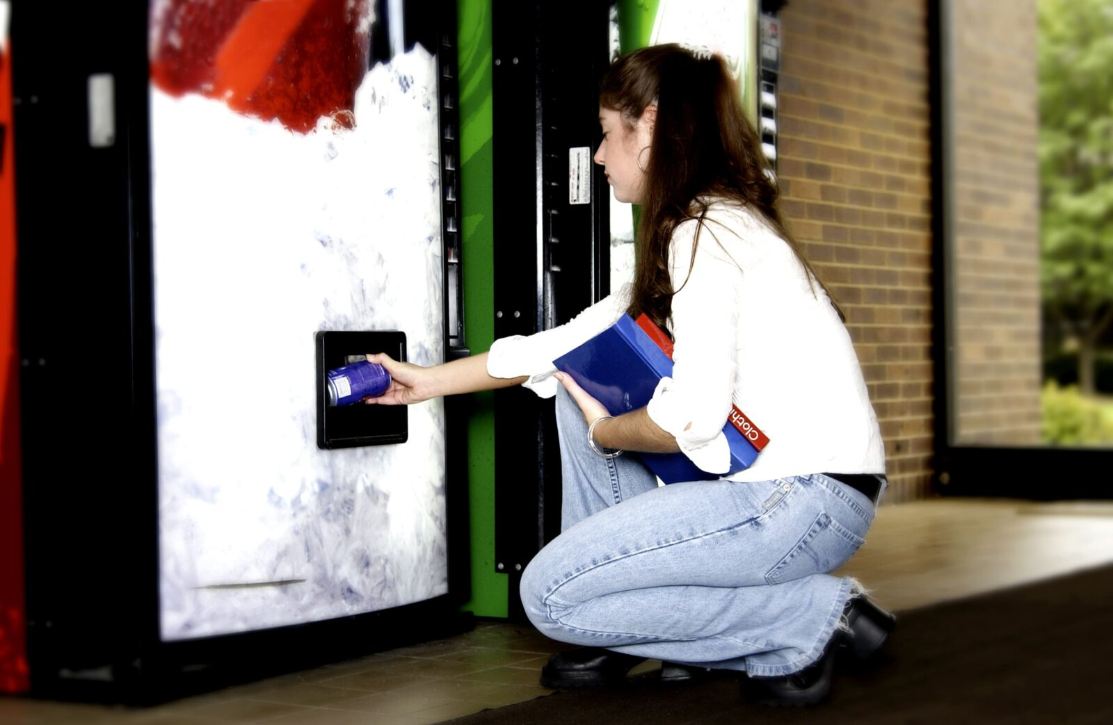 girl reaching into vending machine and holding books in the other hand