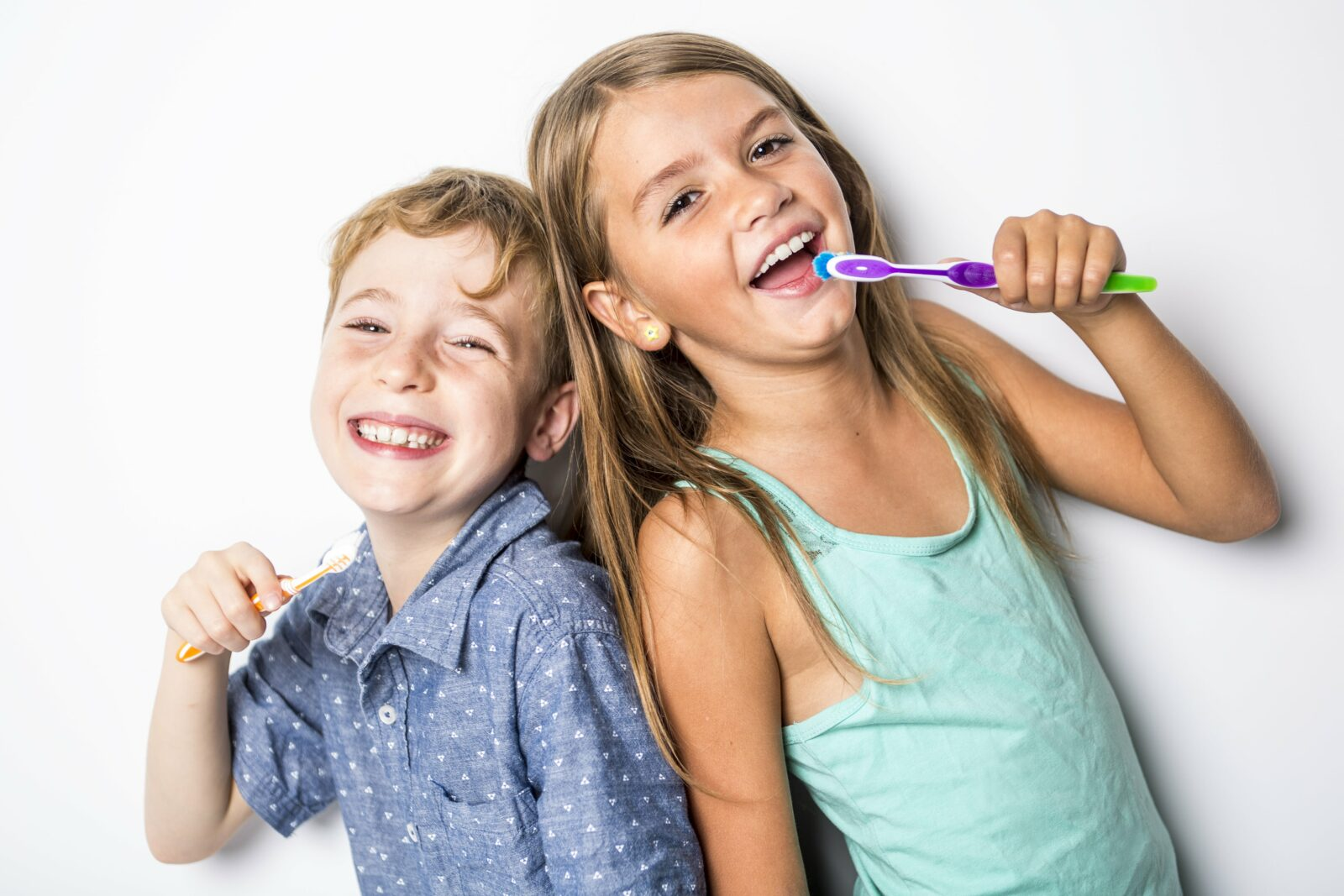 brother and sister brushing their teeth back to back